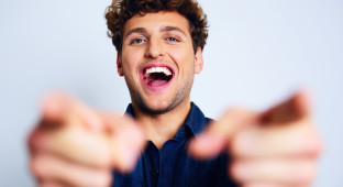 Portrait of a laughing man pointing at you