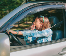 Tired young woman driving car and yawning