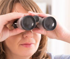 Beautiful woman Looking through binocular at home