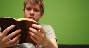 Young blond man reading the Bible with bright green background