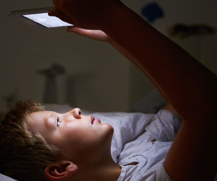 Boy Looking At Digital Tablet In Bed At Night