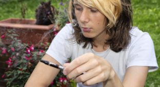 A teenage boy sitting in a garden, smoking an electronic cigarette and exhaling vapour
