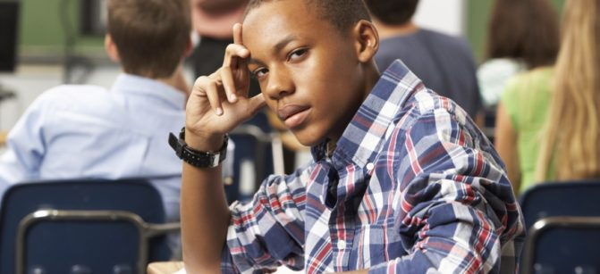 Bored Male Teenage Pupil In Classroom Looking At Camera Leaning On Arm