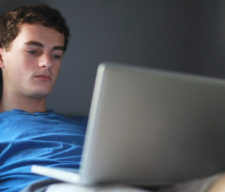 Teenage boy in room using laptop