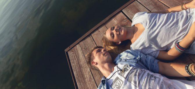 Young Couple Relaxing Near River Enjoying Sunny Day