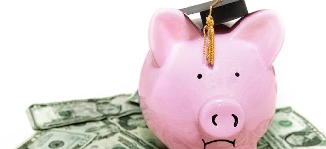 frowning piggy bank with graduation cap, on cash
