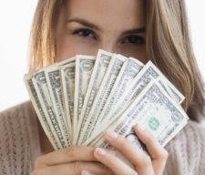 Woman peeking behind money