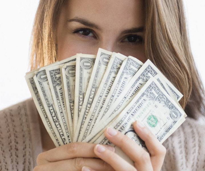 Woman peeking behind money