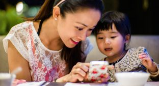 Young mom & toddler using smartphone before dinner