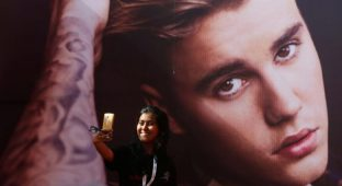 A girl takes a selfie in front of a hoarding outside the venue of Canadian singer Justin Bieber concert in Mumbai, India May 10, 2017. REUTERS/Shailesh Andrade