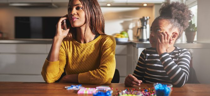 Mother talking on phone forgetting child that wants to play