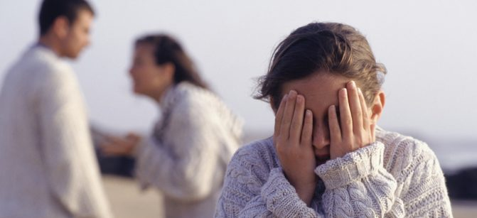 Couple arguing, girl (12-13 years) covering eyes with hands, waist up