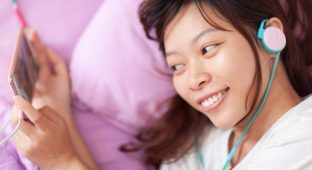 Asian young girl watching mobile video smart phone wear headphones lying on bed top angle view