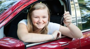 Beautiful blond teenage girl sitting in her new car, holding the keys.
