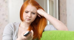 Red-haired  teenager girl  having disappointment  after phone call