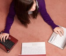 Young woman multitasking with three laptop lying on floor