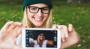 Blonde woman taking self portrait, selfie concept