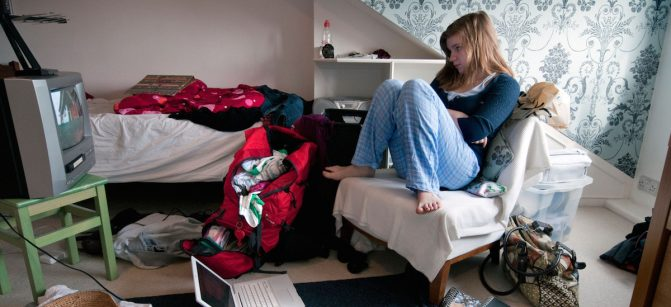 Teenaged girl watching television in messy bedroom