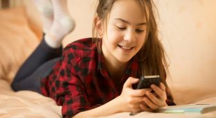 Portrait of smiling teenage girl ling on bed and using smartphone