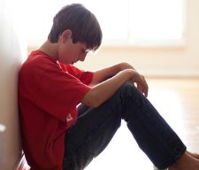 Boy sitting against wall