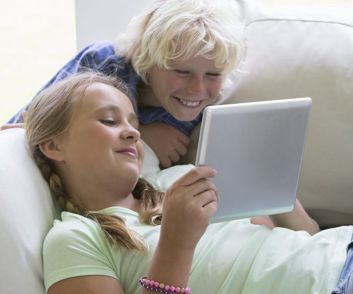 Smiling brother and sister ipad girl Middle