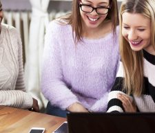 Multi ethnic young girls studying together at home, on computer