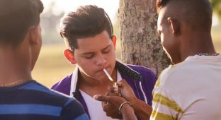 Youth culture, young people, group of male friends, mixed race teen outdoor, teenager in park. Hispanic kid smoking cigarette, confident boy, smoker. Health problems, social issues. Cigarettes