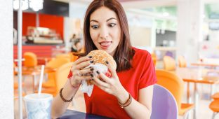 Pretty young funny woman eating hamburger inside in fast-food restaurant