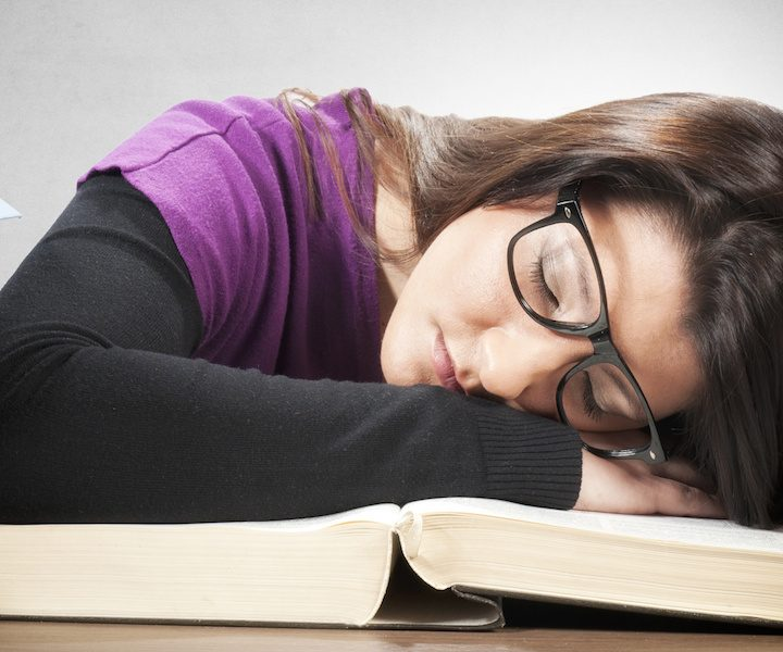 Tired female student sleeping on the big book