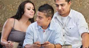 Clever Hispanic teenager watching parents watch his text messaging