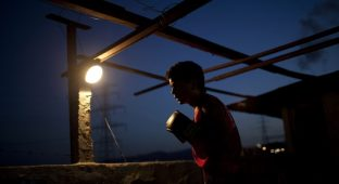 "Javier Apolinar, 14, practises Olympics-style street boxing during a training session at a gym in the low-income neighborhood of La Vega in Caracas February 10, 2011. ""Boxeo Olimpico de Calle"" (Olympic Boxing Street) is an initiative of several institutions of the Venezuelan government, which aims to keep children off gangs and drugs in an attempt to combat high crime rates in the Caribbean nation. The program seeks to promote values such as discipline and respect and show that a better future is possible in a country that has nurtured several boxing champions. Picture taken February 10, 2011. REUTERS/Carlos Garcia Rawlins (VENEZUELA - Tags: SPORT BOXING SOCIETY) - GM1E7321SQB01"