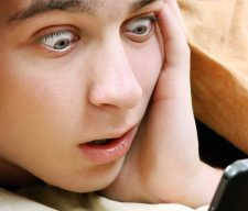 Surprised Teenager with Cellphone under Blanket at the Home
