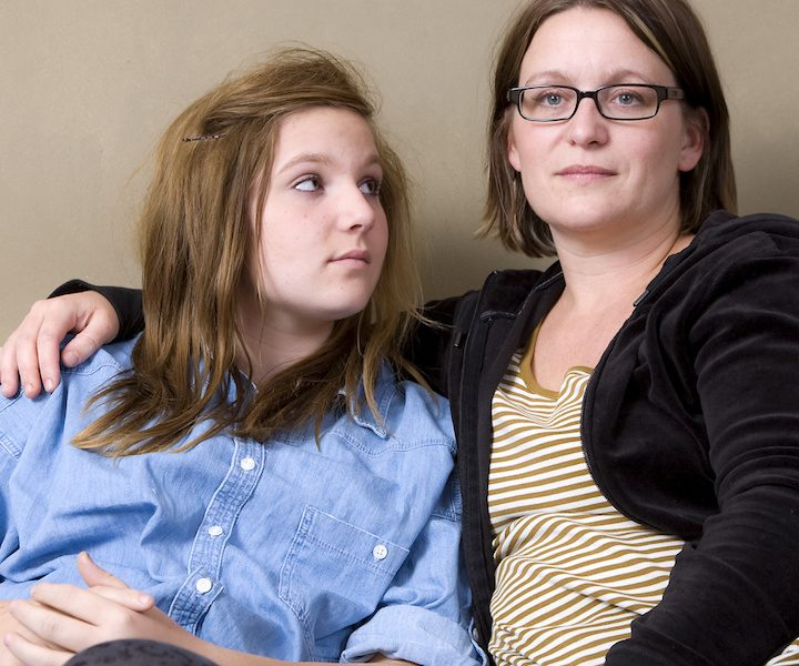 Mother and daughter sitting in sofa. Mother has an absent look