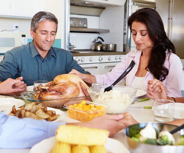Family Sitting Around Table Saying Prayer Before Eating dinner