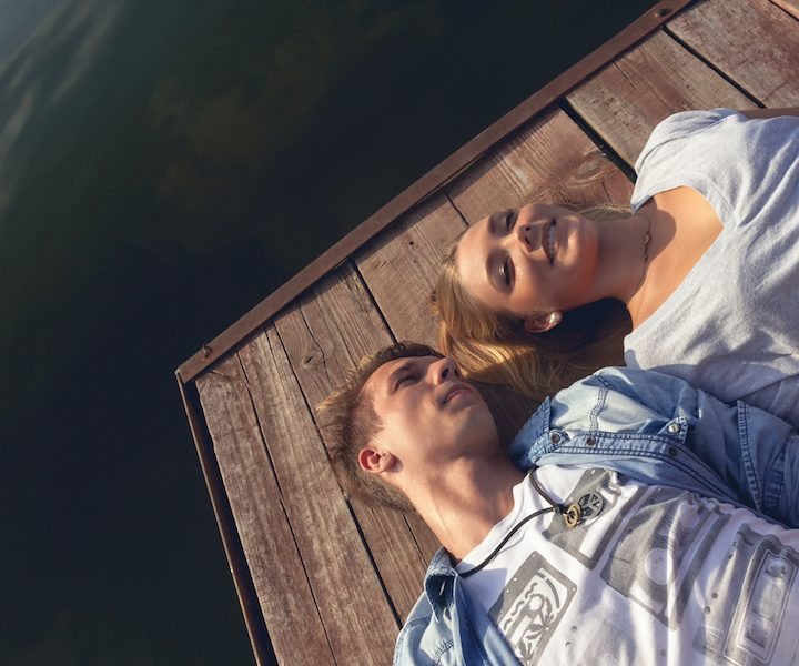 Young Couple Relaxing Near River Enjoying Sunny Day