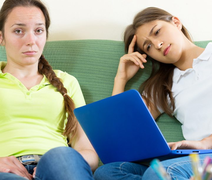 Two sad student sitting on the couch and working on laptop computers. Focus on the left woman