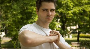 Attractive confident young man in nature environment holding fist with other hand