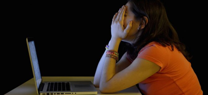 Young student woman alone at desk with computer crying desperate suffering cyber mobbing and bullying