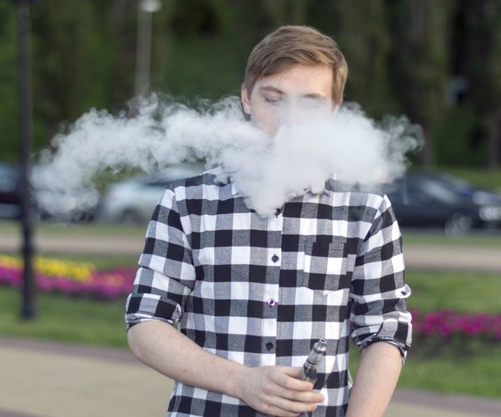 A young man smokes an electronic cigarette and uses a gyroscope.