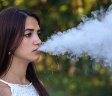 serious cute woman vaping in the park