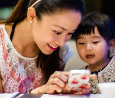 Young mom & toddler using smartphone cell parent  dinner