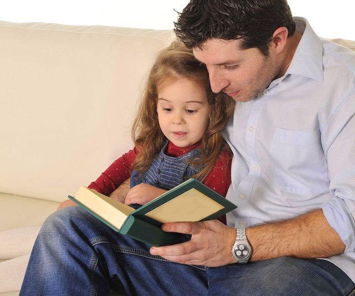 Father and sweet  little daughter reading book on couch together