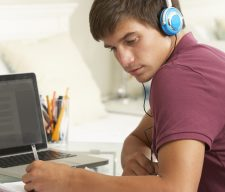 Teenage Boy Studying At Desk In Bedroom Wearing Headphones