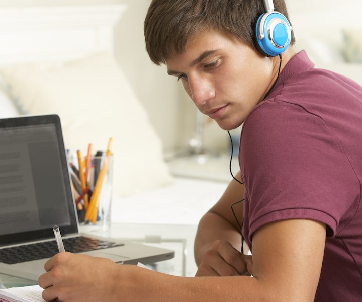 Teenage Boy Studying At Desk In Bedroom Wearing Headphones