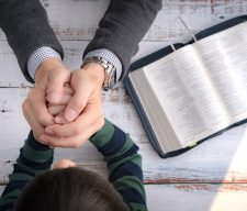 Dad family father and his little son's hands praying together after bible study in the morning. Christianity, Parenting and Raising child in God's way, Thankful moment, Happy father's day.