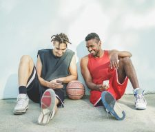 Young cheerful basket ball players having fun with smart phone outdoor - Best sport friends sharing free time with new trends technology - Technology and sporty lifestyle concept - Warm retro filter