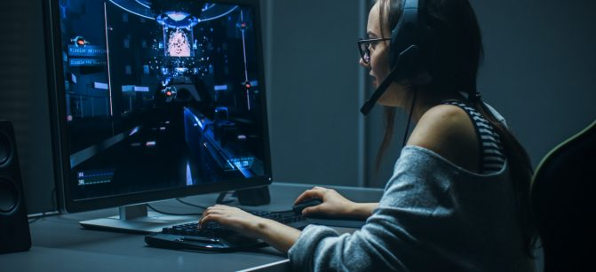 Beautiful Professional Gamer Girl Playing in First-Person Shooter Online Video Game on Her Personal Computer. Casual Cute Geek Girl Wearing Headset. In the Underground Gaming Club.
