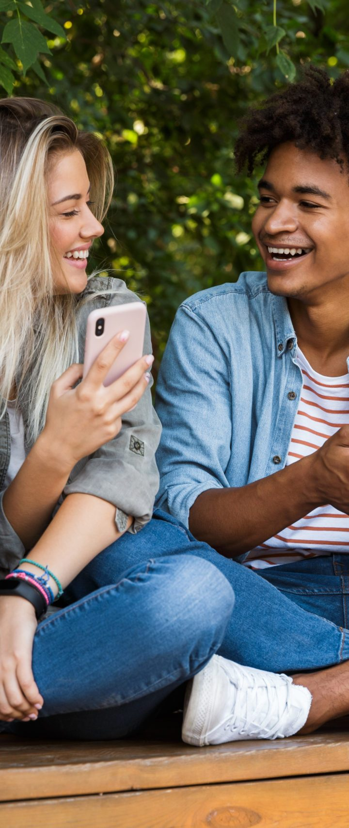Image of excited emotional young loving couple using mobile phone outdoors in park.