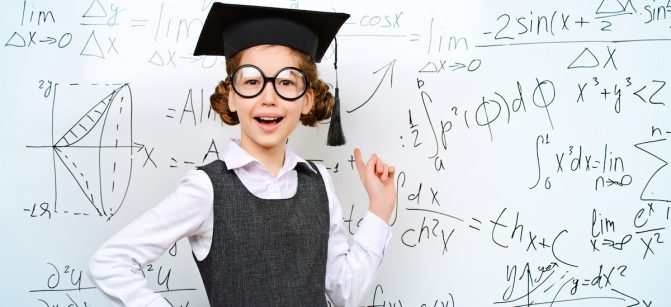 Happy smart schoolgirl in big glasses and academic hat performs the task at the blackboard. Education.