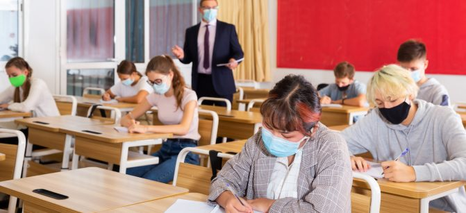 Focused teenage students in protective face masks studying in classroom with teacher, writing lectures in workbooks. Necessary precautions in coronavirus pandemic